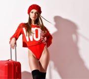 Den unga sexiga kvinnan i röd kropptorkduk för mode och hatten med handelsresandebagage hänger löst på vit royaltyfri foto