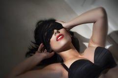 Den unga sexiga kvinnan med snör åt skyler på ögon Royaltyfria Foton