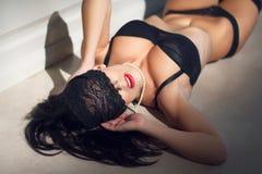 Den unga sexiga kvinnan med snör åt skyler på ögon Royaltyfri Fotografi