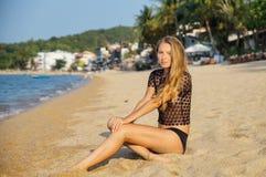 Den unga sexiga kvinnan som nära förlägger och mjuknas, förenar på den bra varma dagen för sommarferie som bär en svart undertröj Royaltyfri Fotografi