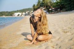 Den unga sexiga kvinnan som nära förlägger och mjuknas, förenar på den bra varma dagen för sommarferie som bär en svart undertröj Arkivbild
