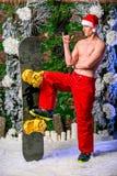 Den unga sexiga sportiga unga mannen i röda flåsanden och julhatt står bredvid en snowboard som rymmer hans fot royaltyfri bild