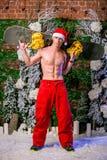 Den unga sexiga sportiga unga mannen i röda flåsanden och jultomten` s cap uppehällesnowboarden på hans skuldror arkivfoton