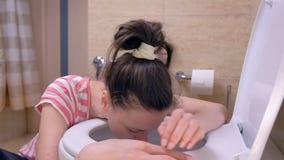Den unga sjuka kvinnan kör toaletten för att spy att sitta på golvet, tecken för matförgiftning lager videofilmer