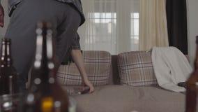 Den unga skäggiga mannen får upp från soffan och går bort och att gripa hans mobiltelefon och hörlurar Suddigt tomt öl arkivfilmer