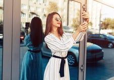 Den unga skönhetkvinnan att göra selfie för självsmartphonen, den utomhus- ståenden, modemodellen, den nätta flickan, hipsteren,  royaltyfri bild