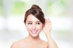 Den unga skönhetkvinnan lyssnar vid örat royaltyfria foton