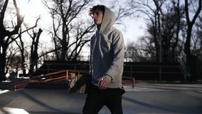 Den unga skateboarderen i grå hoodie går i en skridsko parkerar med en skateboard i händer Sideview l?ngsam r?relse arkivfilmer