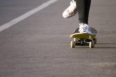 Den unga skateboarderen lägger benen på ryggen ridningskateboarden Royaltyfria Bilder