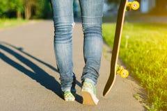 Den unga skateboarderflickan som går med hennes skateboard parkerar in, utomhus Arkivbilder