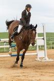 Den unga skickliga ryttarinnan landar den bruna hästen vertikalt Arkivfoton
