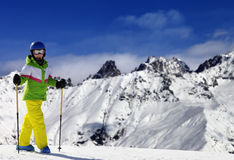 Den unga skidåkaren med skidar poler i snöberg på solvinterdagen Royaltyfria Foton