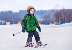 Den unga skidåkaren glider ner från snökullen Royaltyfria Bilder
