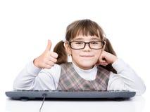 Den unga skolflickan med tangentbordvisning tummar upp Isolerat på vit arkivfoto