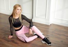 Den unga slanka kvinnan med en idrotts- kropp med långt blont hår, den iklädda svarta sportswearen och rosa damasker, sitter på arkivfoton