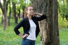 Den unga slanka kvinnan vilar på en trädstam, henne ser rak framåt med en drömlik blick royaltyfri fotografi