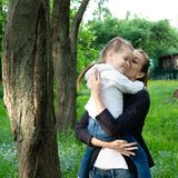Den unga slanka modern rymmer i hennes armar och kramar en dotter arkivbild