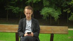 Den unga smartphonen för hipstermanbruk för samkväm knyter kontakt och har en vila i en parkera lager videofilmer