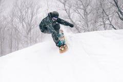 Den unga snowboarderen tappar in i ett halvt r?r royaltyfria bilder