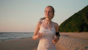 Den unga spensliga kvinnalöparen joggar på stranden på solnedgången på havskusten arkivfilmer