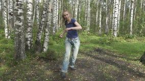 Den unga spensliga kvinnan med långt svetly hår i enskjorta och jeans gör stridighetkampsporter på en skogglänta som är långsam lager videofilmer