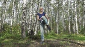 Den unga spensliga kvinnan med långt svetly hår i enskjorta och jeans gör stridighetkampsporter på en skogglänta som är långsam arkivfilmer
