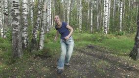 Den unga spensliga kvinnan med långt svetly hår i enskjorta och jeans gör stridighetkampsporter på en skogglänta som är långsam stock video