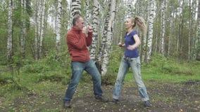Den unga spensliga kvinnan med långt svetly hår i enskjorta och jeans och mannen gör stridighetkampsporter på en skog arkivfilmer