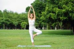 Den unga sportflickan gör yoga Arkivbild