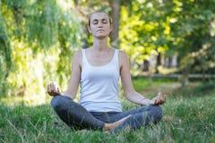 Den unga sportiga attraktiva kvinnan som mediterar på grön sommar, parkerar i lotusblomma poserar Royaltyfri Foto