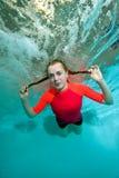 Den unga sportiga flickan är att simma som är undervattens- på en blå bakgrund i en röd baddräkt som ser mig och att le Royaltyfria Foton