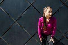Den unga sportiga flickan som bär den rosa sportswearen, kopplar av efter utarbetande utomhus- utbildning, känslig frihet och kop royaltyfri bild