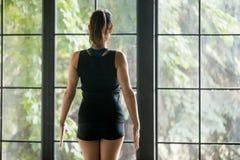 Den unga sportiga kvinnan i berg poserar, fönsterbakgrund, baksida tävlar arkivbild