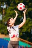 Den unga sportiga kvinnan kastar upp fotbollbollen fotografering för bildbyråer