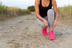 Den unga sportiga kvinnan som binder skon, snör åt utomhus Royaltyfria Foton