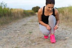 Den unga sportiga kvinnan som binder skon, snör åt utomhus Arkivfoton