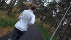 Den unga sportiga kvinnan som kör i hösten, parkerar lager videofilmer
