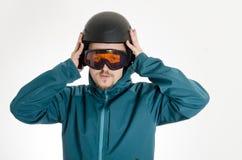 Manen med goggles som sätter på, skidar hjälmen Royaltyfria Bilder