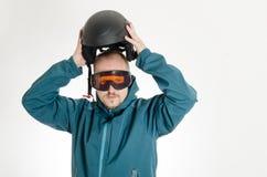 Manen med goggles som sätter på, skidar hjälmen Arkivfoto
