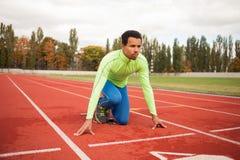 Den unga sportiga mannen är klar att köra på löparbana Passa väl bildat folk på stor trevlig modern stadion royaltyfri foto