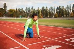 Den unga sportiga mannen är klar att köra på löparbana Passa väl bildat folk på stor trevlig modern stadion arkivbilder