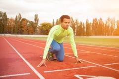 Den unga sportiga mannen är klar att köra på löparbana Passa väl bildat folk på stor trevlig modern stadion arkivfoton