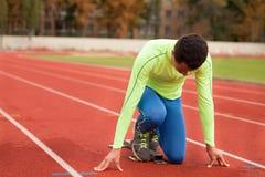 Den unga sportiga mannen är klar att köra på löparbana Passa väl bildat folk på stor trevlig modern stadion arkivbild