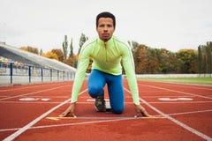 Den unga sportiga mannen är klar att köra på löparbana Passa väl bildat folk på stor trevlig modern stadion royaltyfri fotografi
