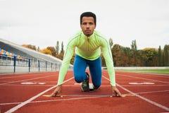 Den unga sportiga mannen är klar att köra på löparbana Passa väl bildat folk på stor trevlig modern stadion fotografering för bildbyråer