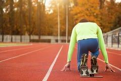 Den unga sportiga mannen är klar att köra på löparbana Passa väl bildat folk på stor trevlig modern stadion arkivfoto