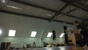 Den unga sportiga mannen kopplas in med rep i idrottshallen lager videofilmer