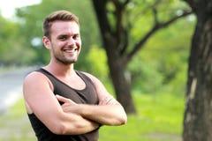 Den unga sportiga mannen som ler och, poserar med den vikta armen Royaltyfri Foto
