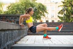 Den unga sportkvinnan som gör övningar under utbildning utanför i stad, parkerar Köra för konditionmodell som är utomhus- Arkivbild