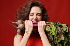 Den unga sportkvinnatuggan äter ny rödbeta med gröna sidor Sunt ätabegrepp på röd bakgrund arkivbild